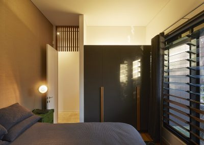 Bedroom with mixed glass and timber louvres adjacent