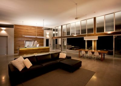 Ceiling fans and louvre windows help keep the living room cool in summer