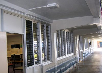 External view of classrooms with louvre windows and security bars by Breezway