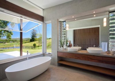 The bathroom uses narrow louvre windows to maximise ventilation and mirror space
