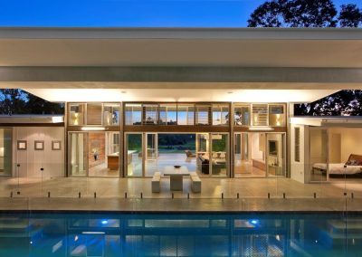 View across swimming pool to large open living area with louvre windows to aid cross ventilation