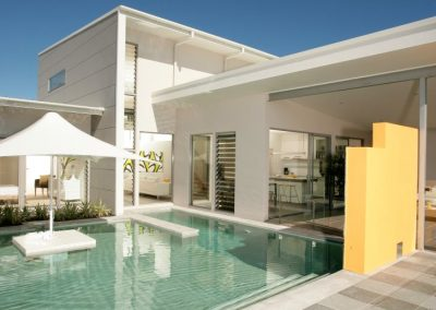 Multiple louvre windows face onto the swimming pool of this new home