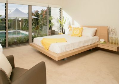 Louvre windows help to connect this bedroom to the swimming pool and outdoor surroundings