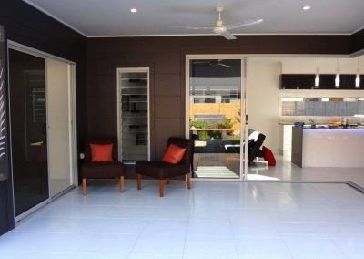 Sliding doors and louvre windows onto outdoor room shades living area and opens home to breezes