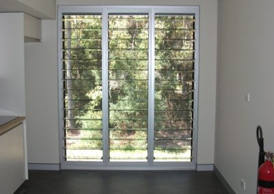 A three bay louvre window in clear anodised framing brings fresh air into the classroom