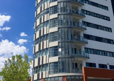 louvre windows with the stronghold system from breezway were used to enclose the balcony on this multi storey apartment building