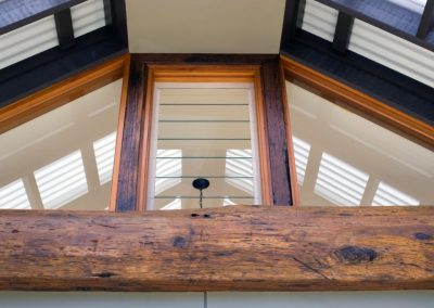 Louvre window in timber frame amongst feature recycled wooden beams