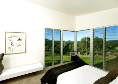 The bedroom uses a combination of louvre windows and fixed glass to frame the view and gives great ventilation