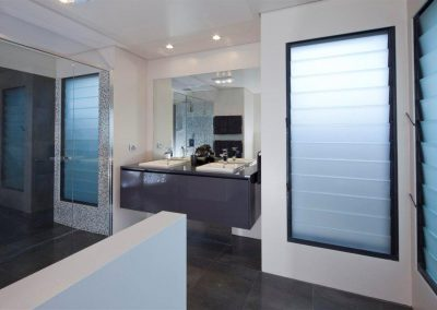 Louvre windows with obsure satina glass provide fresh air and privacy in the bathroom