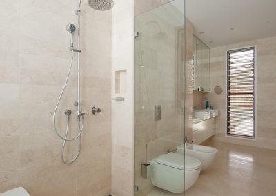 Tall louvre windows provide fresh air and natural light to this bathroom
