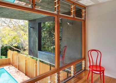 Louvres windows above and below this large fixed glass window provide natural light and ventilation