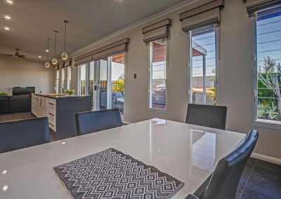 Kitchen and dining room with breezway louvre windows and view to outdoor deck