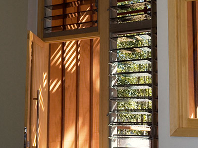 Tall and narrow Breezway Louvres next to front doors keep a view and provide airflow into the home