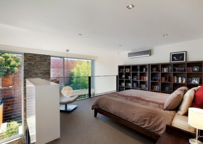 Bedroom overlooking outdoor area through breezway louvres and fixed glass