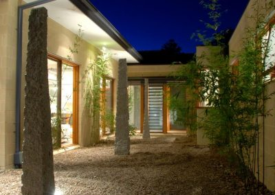 Courtyard at night with breezway louvres in distance