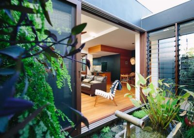 View of japanese garden and living room with breezway louvres in glass link