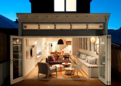 Night view of rear of fairlight house into living room with Breezway louvres