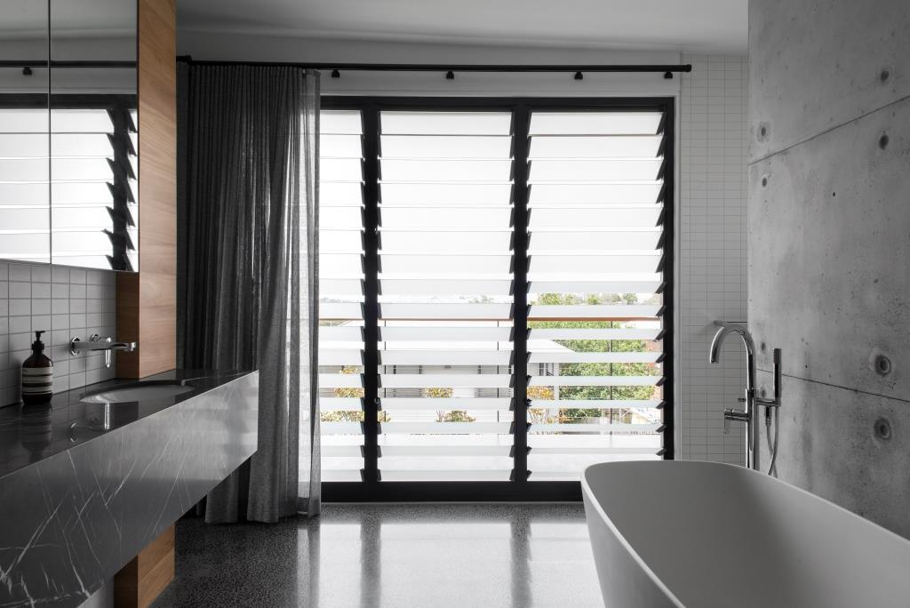 Floor to ceiling Breezway louvres are installed in the bathroom with frosted blades for privacy