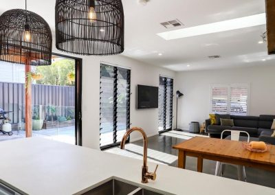 Open plan living area with two double bays of Breezway Louvre Windows